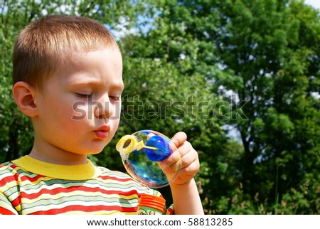A child blowing bubble, background tree
