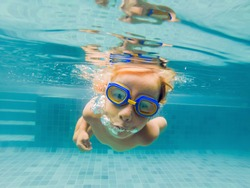 A child boy is swimming underwater in a pool, smiling and holding breath, with swimming glasses