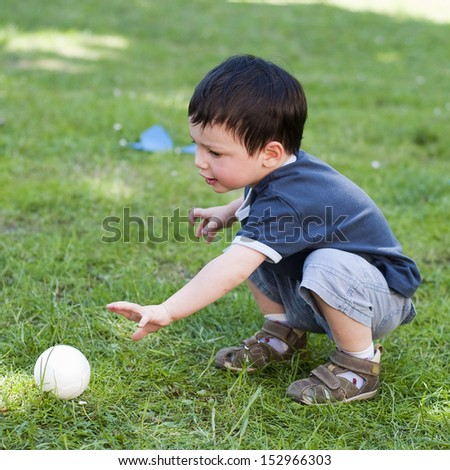 A child boy playing with a small  ball on a grass in the garden.