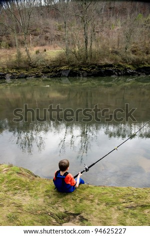 A child catches a fish in the river at the bait