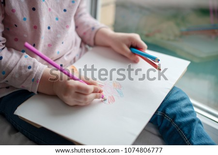 A child draws a flower with colored pencils #1074806777