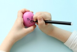 A child draws a funny face on an Easter pink egg with a black marker. Decorating the eggs. Preparing for Easter. Child's play. Selective focus.