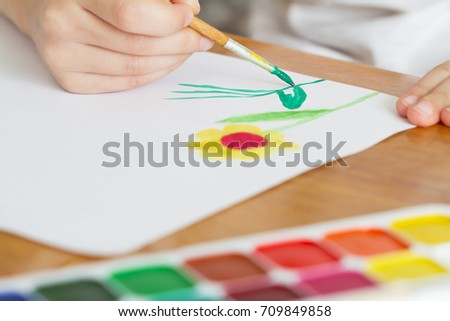 A child draws flowers by paint. Selective focus #709849858