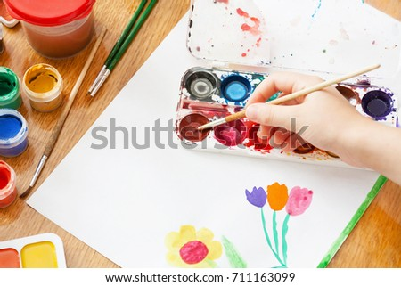 A child draws flowers by paint. Selective focus #711163099