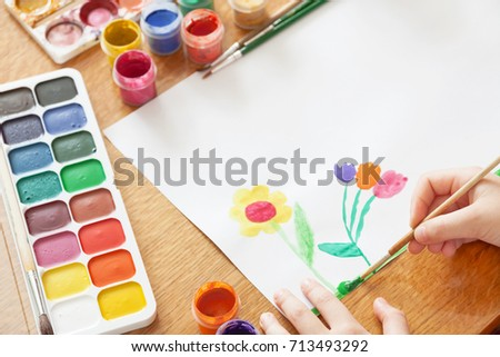 A child draws flowers by paint. Selective focus #713493292