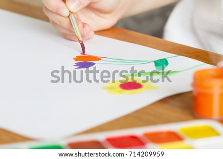 A child draws flowers by paint. Selective focus #714209959