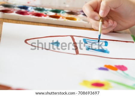 A child draws house and flowers by paint. Selective focus #708693697