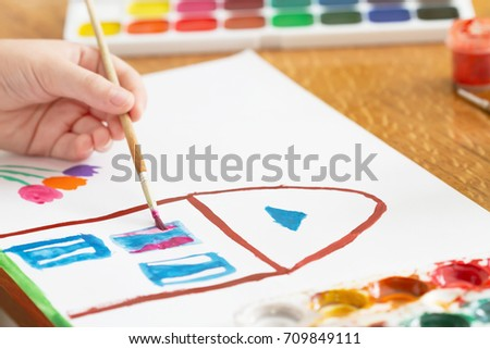 A child draws house and flowers by paint. Selective focus #709849111