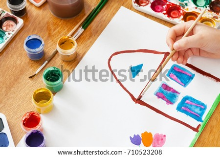 A child draws house and flowers by paint. Selective focus #710523208