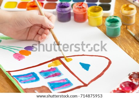 A child draws house and flowers by paint. Selective focus #714875953