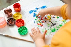 A child draws leafs on a tree. Ideas for drawing with finger paints. Finger painting for kids on white background. Little girl painting by finger hand paint color. Children development concept.