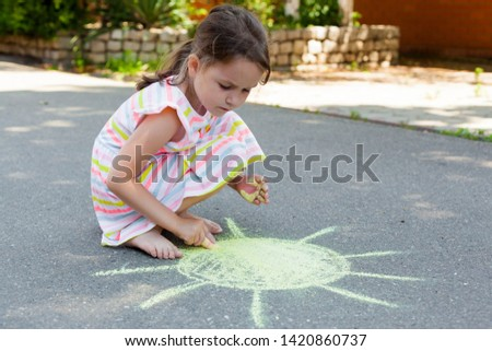 a child draws with chalk the sun on the pavement. Summer outdoor activity concept, drawing with chalks on asphalt