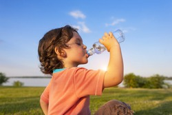 A child drinks water from a bottle while walking, baby health.