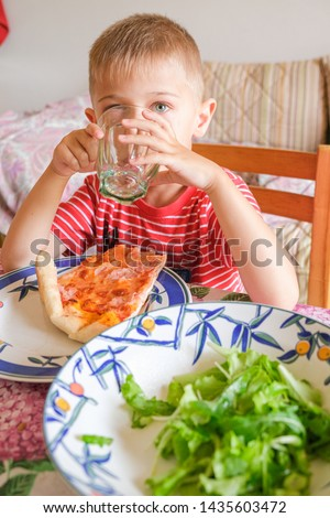 a child eats a slice of pizza and salad