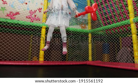 A child girl in a beautiful festive dress jumps on a trampoline with soft net fence in modern kids playing room in the kindergarten indoor play zone Stock fotó ©