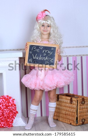 A child girl in pink tutu skirt dress holding a chalkboard saying be my valentine in a blond wig