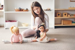 A child girl plays with dolls, a girl in a dance costume is engaged in gymnastics and ballet with a doll, role-playing and story games, sports and stretching, gentle colors