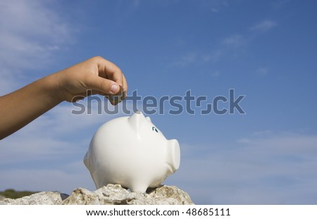 A child hand putting a euro coin on a piggy bank