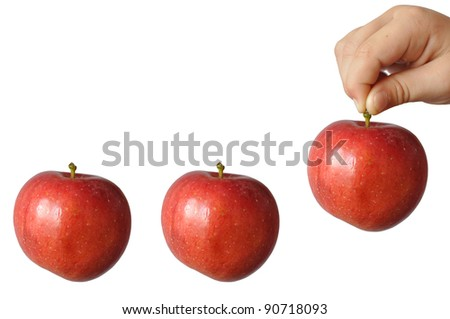 A child holds a large red apple fruit stem and wants to put him last among the other two, in isolation