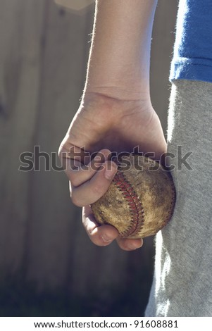 A child holds a used baseball and is about to throw it, copy space