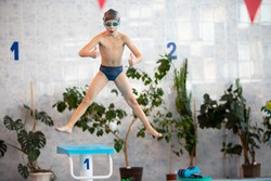 A child in a cap and swimming goggles jumps into the pool. Swimming section.