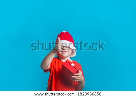 A child in a Christmas Santa Claus costume shows a like on a blue background in the Studio. The boy has hidden his eyes under a red hat and is holding a gift box in his hand. stock photo
