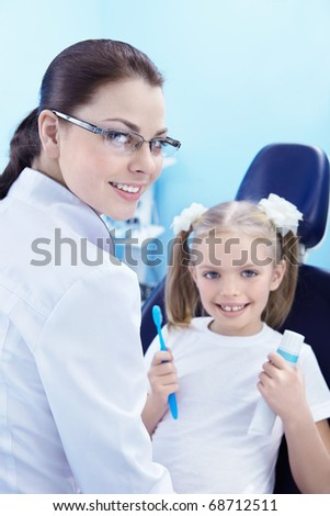 A child in a dental chair with a toothbrush and toothpaste