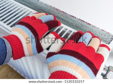 A child in bright warm wool gloves warms his hands on a heating radiator. The symbolic image of the heating season at home. Part of body, selective focus.