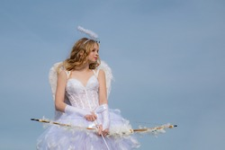 A child in the clothes of an angel on sky background. Little angel in love. Lovely girl cupid with bow and arrow is ready to find your love. Lovely child.