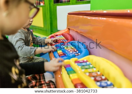 A child is playing on a children's musical instrument #381042733