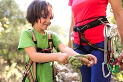 A child learns to knit the safety knot from the rope. Climbing rope for belaying. A little boy is trying to tie a knot. Scout training. Children's hands and safety rope. Teaching children.