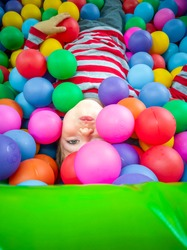 A child lies among colorful balls on children's play area with multicolored balls and slide. Kids fun activity consept. Children's leisure