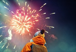 A child looks at the New Year's Eve Fireworks on the sky