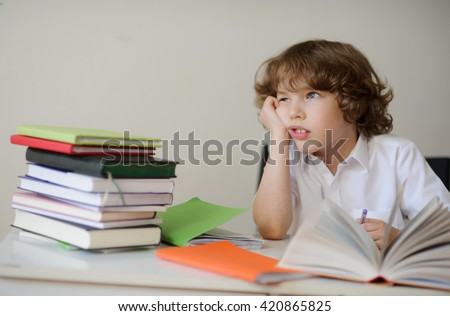 A child of primary school age do homework. The boy does his homework at his desk at home. The student / pupil has been bored on the lesson.