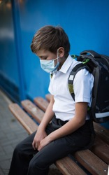 A child of the European race sits sad on a bench with a knapsack and a protective medical mask. A schoolboy goes to school in the midst of the COVID-19 pandemic. Go to school wearing masks.