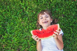 A child on a picnic eats a watermelon. Selective focus. Food.