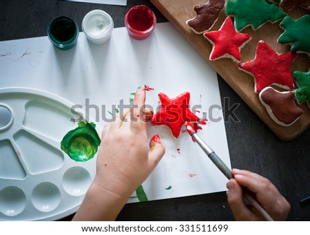 A child paints the colors of Christmas toys made of dough.