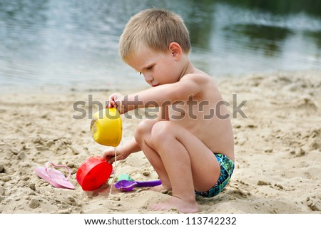 A child playing in the sand on the river bank