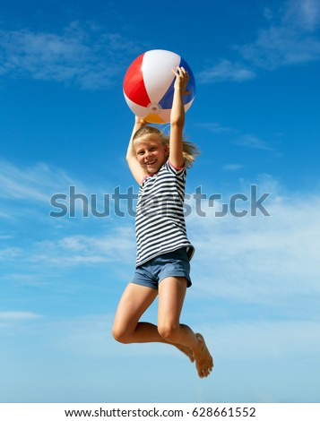 A child playing with a ball on the beach. The concept of summer vacation