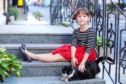 A child playing with a cat on the steps of the house. A young girl holds a black cat. Children play with pets. Children and pets. A girl helps a homeless cat on the street. Pets and lifestyle concept.