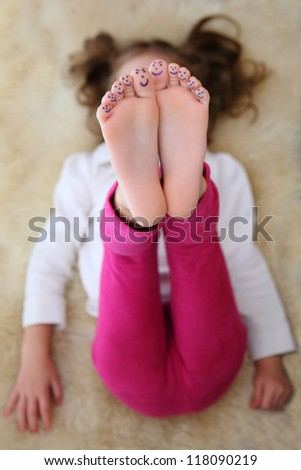 A child plays sports with a face painted on the toes