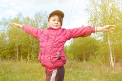 a child poses against the background of the forest. The girl's arms are spread wide at her sides . The photo is deliberately tinted in yellow shades