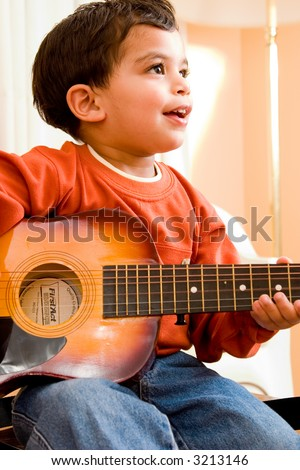 A child practices playing the guitar