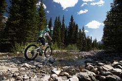 A child rides a mountain bike through a cascade creek along the High Rockies Trail in Kananaskis Alberta Canada.