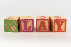 A child's alphabet toy spelling word block set, spelling out the word play across the frame