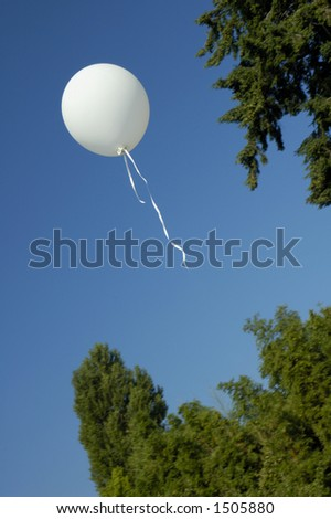 A child's balloon floats away into a clear blue summer sky.