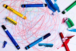 A Child's Crayon Drawing/scribbles with Generic Crayons and torn lable pieces from stripping the label.  The center of the image is open for Copy Writing.