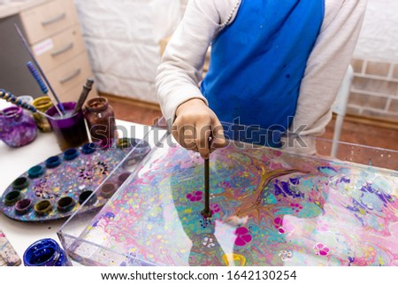 """A child's hand closeup forms a pattern of paints on the surface of the water with the help of a special tool - Ebru Art, the Ancient Techniques of """"Painting on Water"""""""