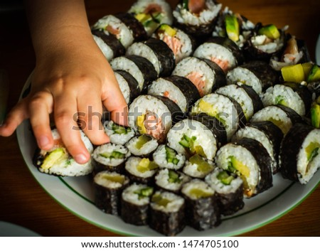 A child's hand grabbing a piece of sushi with vegetables from the plate, the picture shows futomaki sushi with baked fish salmon and hosomaki with pickled radish and cucumber