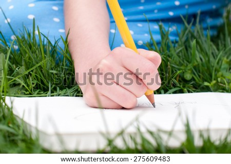 A child\'s hand holds a yellow pencil and draws in a sketchbook.  The child is sitting in the grass and her blue dress is visible in the background